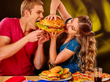huge: Woman and man feed each other fast food. Concept.