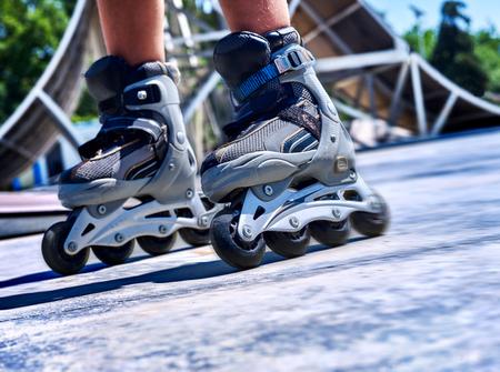 blading: Kids feet wearing roller skate  in skatepark. low section.