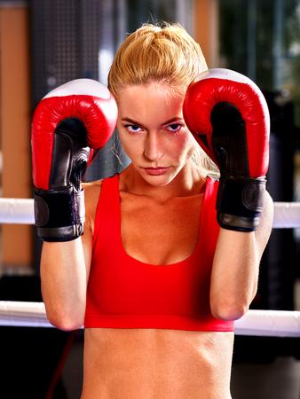 sports venue: Portrait of sport agressive girl boxing wearing red.