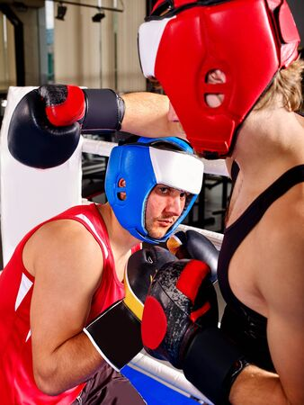 circular muscle: Two young strong men boxer wearing helmet are boxing. Stock Photo