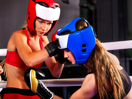 agressive: Two agressive women boxer wearing helmet boxing at ring .