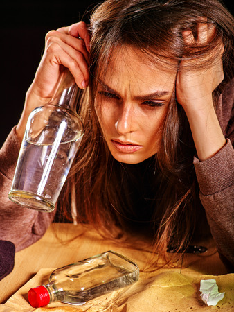 bad habit: Drunk girl holding bottle of alcohol. Soccial issue alcoholism on black background.