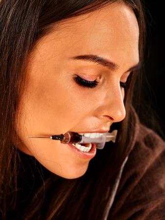 tourniquet: Portrait of female drug addict with syringe in teeth.