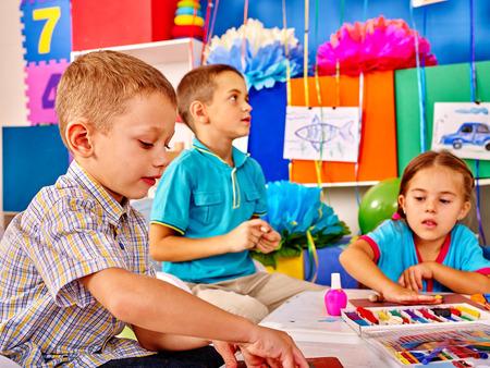 Bambini piccoli gruppi di stampo da plastilina nella scuola per principianti.