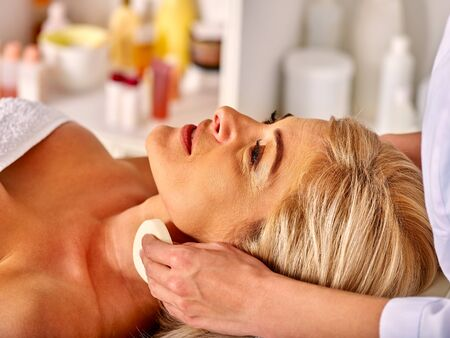 Lying woman middle-aged on procedure  face cleaning in spa salon. Stock Photo