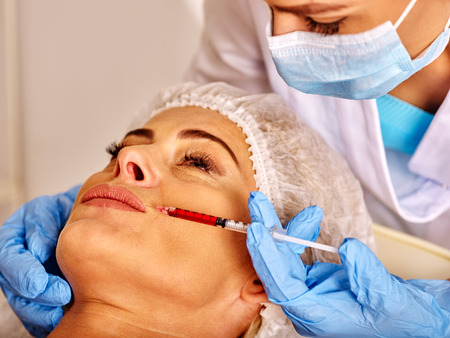 35 40 years old: Woman middle-aged in spa salon with doctor. Beauty woman giving anti-ageing injections.