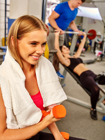 sport woman: Woman with towel on sholders working his arms and chest at gym. She lifting barbell.