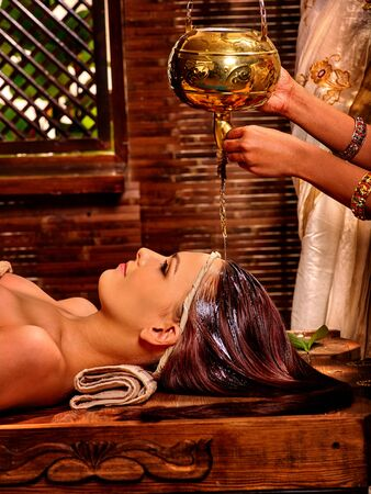 wooden aromatherapy: Young woman having pouring oil lamp Ayurveda spa treatment.