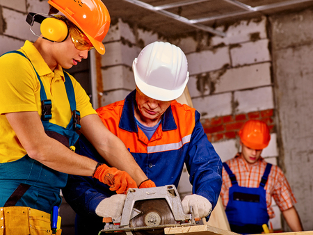 Working group people builder with circular saw. Brick wall in background. Stock Photo