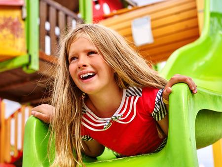 cabeza abajo: La muchacha del ni�o boca abajo en juego parque de juegos.