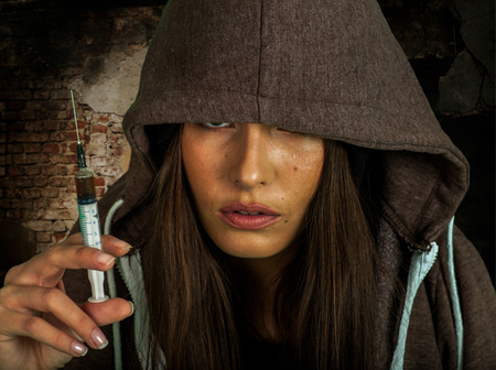 Portrait of  woman addicted to syringe on  brick wall background. Stock Photo