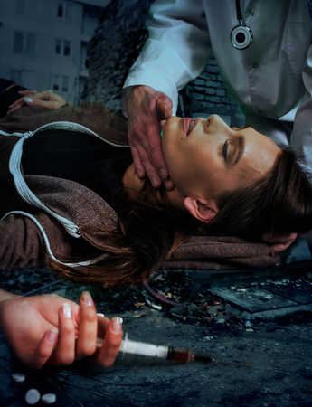 illicit: Portrait of  woman addicted to syringe on  brick wall background. Stock Photo