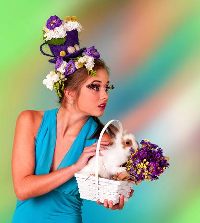 false eyelashes: Woman with false eyelashes  and flowers in hair holding easter bunny. Stock Photo