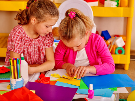 colored paper: Two girls friend  kids gossip and craft colored paper on table in kindergarten . Stock Photo