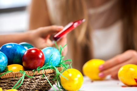 kids club: Children paint Easter eggs at home. Sharpness on rainbow eggs. Blurry girl background. Stock Photo