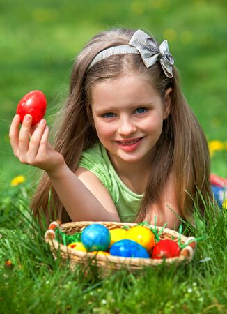 finds: Happy child finds easter basket outdoor. Girl show finding red egg on green grass. Stock Photo