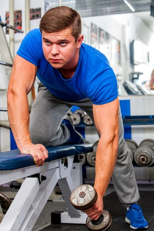 health woman: Strong man working with  dumbbells his body at gym. Stock Photo