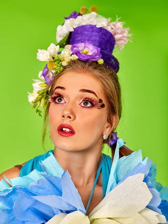 false eyelashes: Portrait woman with false eyelashes with easter hairstyle holding  flowers. Green background. Stock Photo
