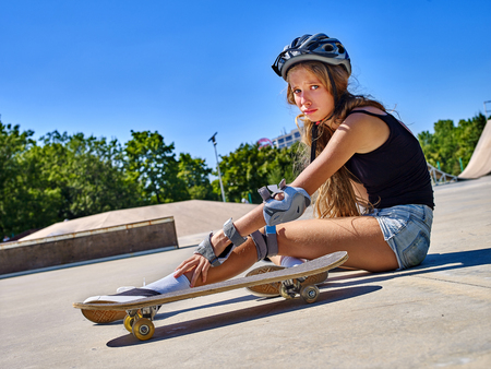 Sport girl with injury sitting near her skateboard outdoor.