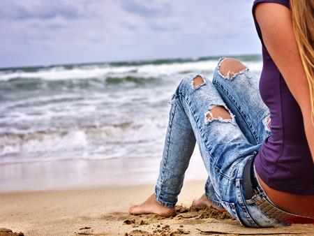 in jeans: mar chica del verano. La mujer llevaba en los pantalones vaqueros con agujeros que se sienta en la costa cerca del océano con olas. Caliente autofoto pata de perro.