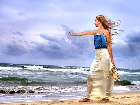storm sea: Summer girl sea.  Proud woman goes on coast before storm. Stock Photo