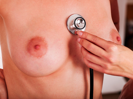 breast examination: Nude female breasts and doctors hand close-up with stethoscope. Stock Photo