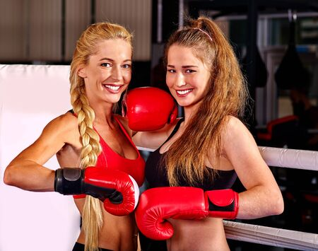 martial arts woman: Two  women boxer wearing red  gloves posing in ring. Martial arts.