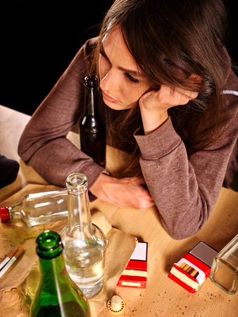 degradation: Drunk girl holding bottle of alcohol on table. Soccial issue alcoholism. Top view. Stock Photo