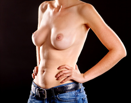 breast examination: Body of unrecognizable girl with beautiful naked breasts in jeans on black background. Stock Photo