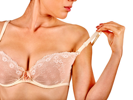 Woman in  bra strap straightens. Nursing mother examines her nude breasts.