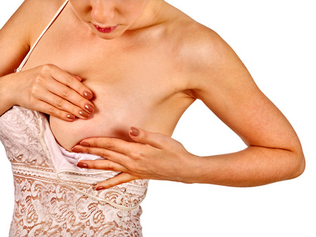 senos: Mujer joven en cuestión examina sus pechos desnudos. Aislado.