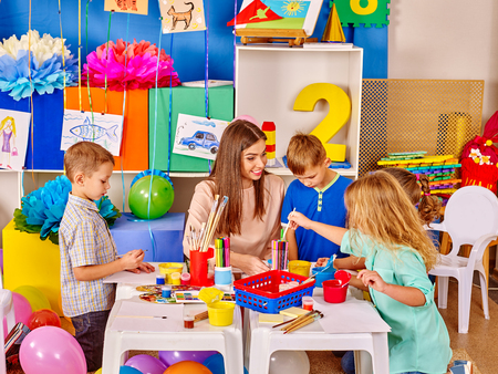 kindergartener: Group of kids with female teacher painting  together in  kindergarten . Stock Photo