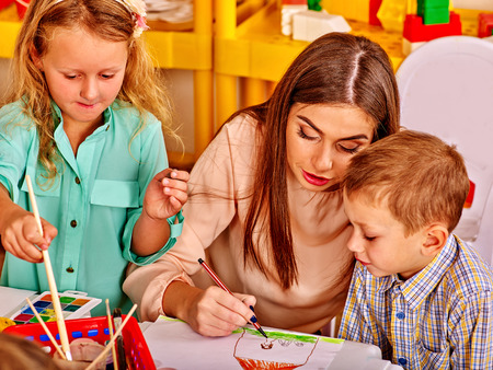 children painting: Children with teacher woman painting on drawing lesson  in  kindergarten .