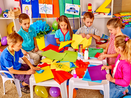children drawing: Group kids holding colored paper on craft lesson in kindergarten .