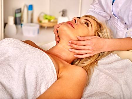 35 40 years old: Woman looking up middle-aged take face and neck massage in spa salon.