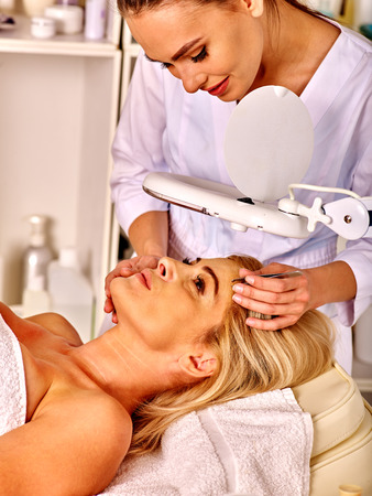esthetician: Woman middle-aged in spa salon with young beautician. Tweezing eyebrow under lamp by beautician.