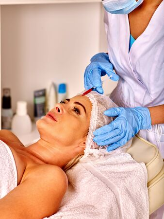 antiaging: Woman middle-aged in spa salon with beautician. Female giving anti-aging injections.