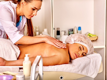 35 40 years old: Woman wearing hat middle-aged take back massage in spa salon with young beautician. Stock Photo