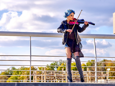 play popular: Music street performers girl violinist with blue hair playing  aganist sky with clouds outdoor. Freedom concept.