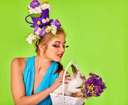 pestaÑas postizas: Mujer con las pestañas falsas y flores en el pelo celebración de conejo de Pascua en el fondo verde.