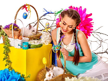 animal sexy: Woman in easter decorated interior holding eggs and group of two rabbits baskets.