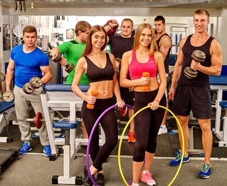 woman lifting weights: Group of people working with  dumbbells and hoop his body and posing camera at gym.