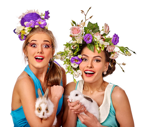 Two admiration women in easter style keep rabbits and flowers. Isolated.