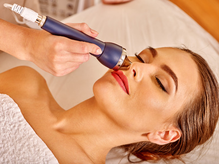 Head of young woman receiving dark blue electric ultrusound facial massage at beauty salon.