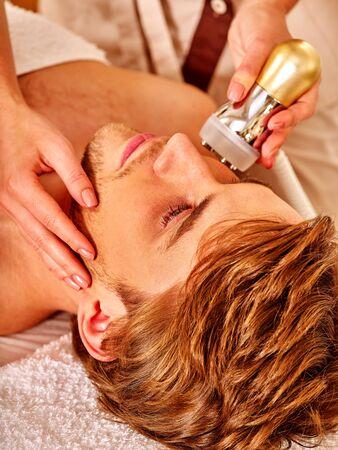 ni�as sonriendo: Cerca del hombre apuesto que reciben terapia facial electroporaci�n en el sal�n de belleza.