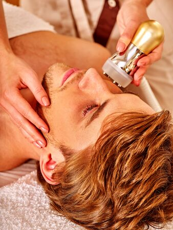 healthy girls: Close up of handsome man receiving electroporation  facial therapy at beauty salon.