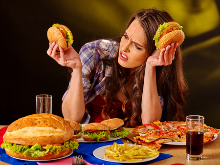 comida chatarra: Muchacha infeliz comer comida rápida barata hamburguesa grande y pizza.