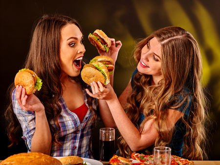 personas saludables: Mordedura de las muchachas hamburguesa con dos lados. concepto del humor de la comida rápida.