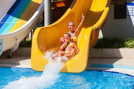 kids playing water: Two girls sisters on water slide at aquapark.