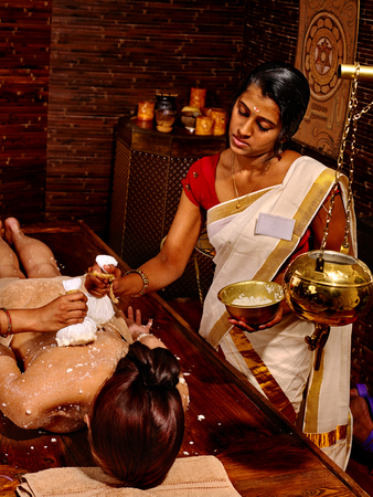 girl in nature: Woman luxuriating in ayurvedic massage with pouch of rice. Stock Photo